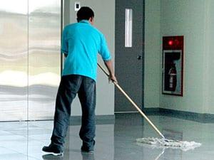 Conserje pasando mopa industrial en el portal